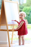 Toddler girl drawing on white board standing next window