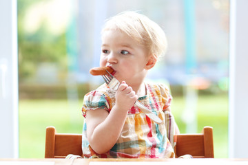toddler girl eating biting on sausage from metal fork