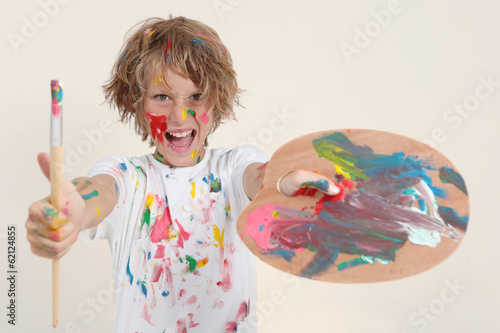 boy painting with brush and pallete