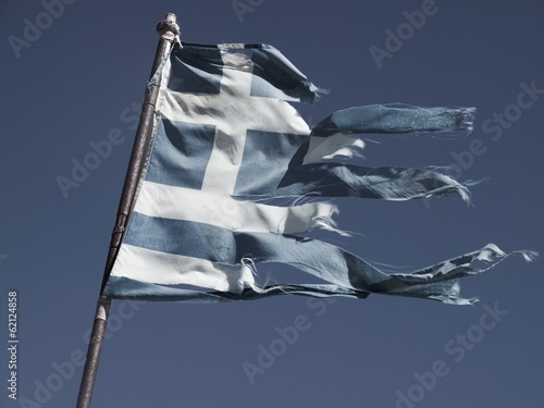 Old and torn flag of Greece on dark blue sky