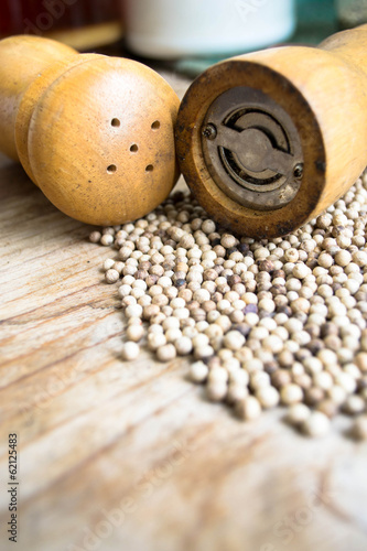 Pepper mill and pepper on wooden background