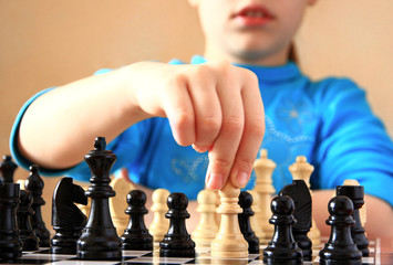 Little girl playing chess indoors.