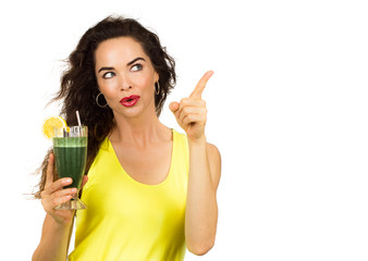 Woman holding green smoothie and pointing
