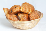 Croissants et pains au chocolat dans une corbeille sur fond blan - 62127854