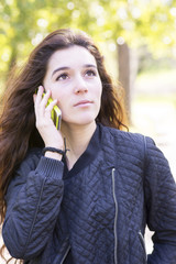 Portrait of pensive and serious girl talking by phone, outdoor.