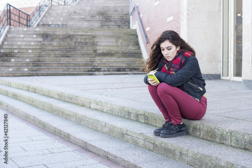 Young serious and pensive woman using mobile phone, sitting of s
