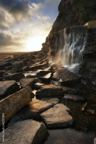 Beautiful landscape image waterfall flowing into rocks on beach