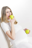 portrait of pregnant woman eating green apple