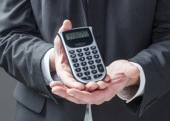 business man displaying figures on calculator
