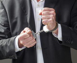 corporate offense with man in handcuffs