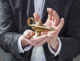 corporate man hands holding Aladdin lamp for making a wish