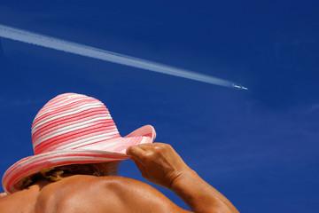 Flugzeug über einer Frau mit Sonnenhut