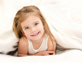 Adorable little girl waked up in bed