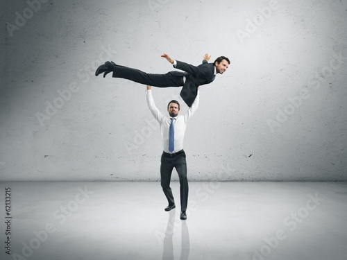 One businessman lifting the second one and helping him to fly