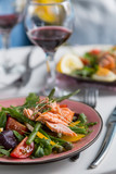 salad with salmon and verdure in plate on table with blue chair
