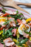 salad with salmon and verdure in pink plate on retro newspaper b