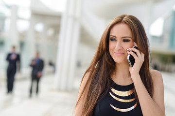 Beautiful young woman in urban background talking on phone