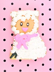 Spring themed cookie decorated as a sheep on pink background