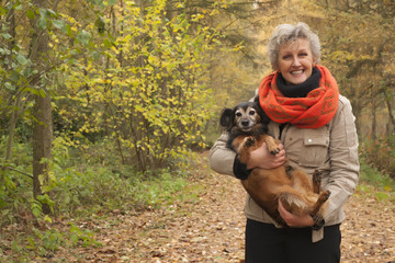 Middle aged woman is carry the dog