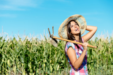 Happy female farmer in corn field
