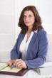 Senior Manager weiblich: Portrait sitzend im Büro