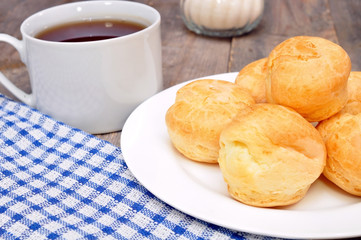 profiteroles and a cup of tea on a wooden table