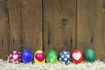 Hintergrund Holz mit bunten Ostereiern zu Ostern
