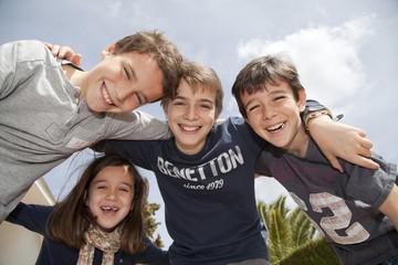 Niños sonriendo cogidos por los hombros