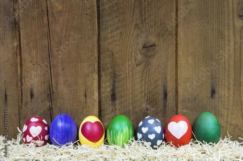 canvas print picture Hintergrund Holz mit bunten Ostereiern zu Ostern