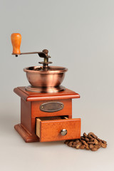 Coffee grinder with coffee beans vertical on gray background