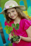 Gardening, planting - girl with strawberry seedling