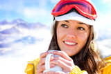 Female skier drinking coffee.
