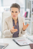Portrait of business woman in office explaining something