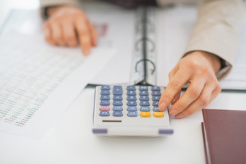 Closeup on business woman using calculator