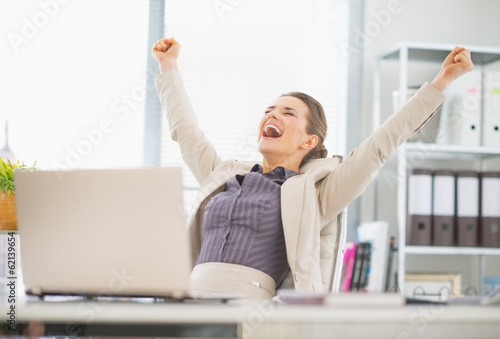 Portrait of happy business woman in office rejoicing success - 62139654