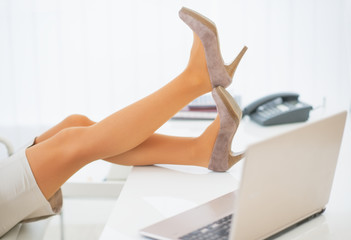 Closeup on business woman having break and relaxing legs