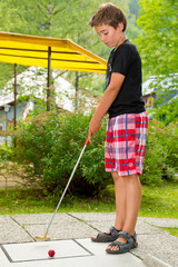 Junge beim Minigolf spielen