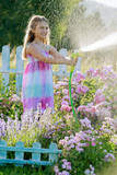 Summer fun - lovely girl has fun watering flowers