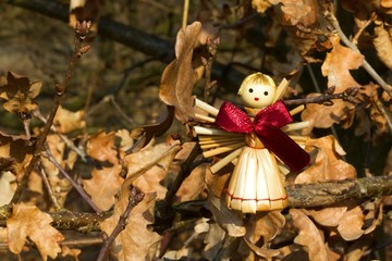 Straw angel figurine in the wood