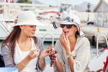 Happy women on the bow of a Sail boat eating a grapes fruit.