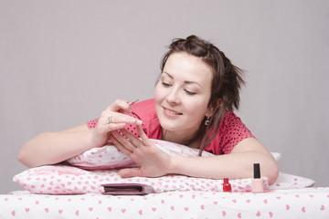 девушка красит ногти лежа в постели
