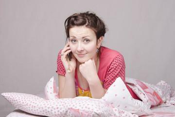 девушка разговаривает по телефону лежа в постели