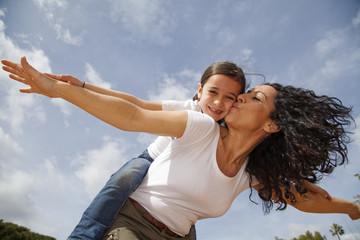 Madre besando a su hija mientras juegan a volar