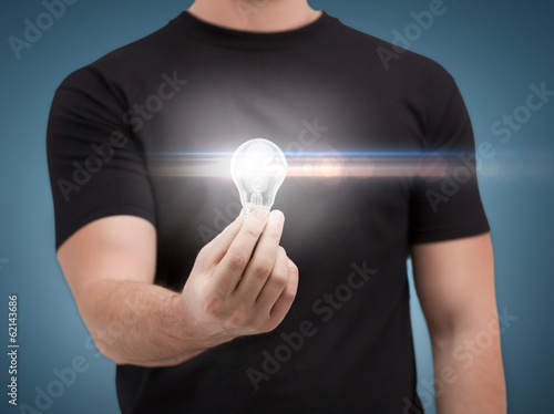 close up of man holding light bulb