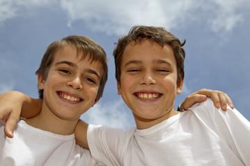 Niños cogidos por los hombros sonriendo