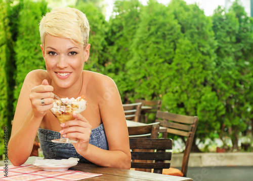 Close-up of young women eating fruit salad outdoors in the resta