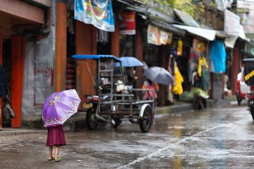 Little girl in the rain on a Philippines street