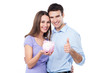 Couple holding piggy bank and showing thumbs up