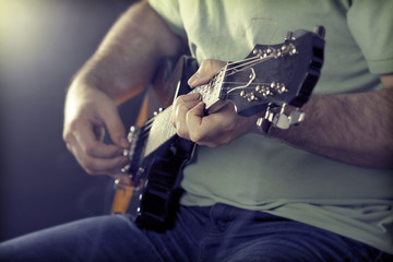 Close up on man`s hand playing guitar