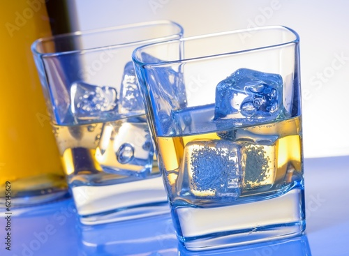 two glasses of whiskey with ice on blue light
